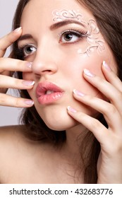 Close-up portrait of beautiful young woman with face art  make up and manicure
