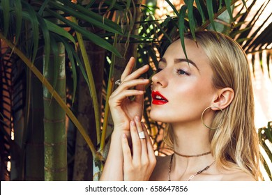 Close-up portrait of a beautiful young woman with long blonde hair, green mysterious eyes and red big sexy lips posing next to the palms tree. Her looks is complemented by golden accessories.