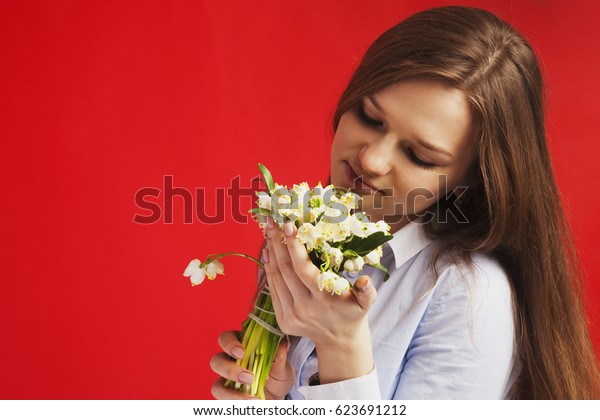 Close-up portrait of Beautiful young woman enjoying nature. Happy female smell a flower with close eyes on red background. (Pleasure, nature, travel, vacation)