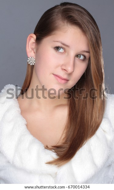 Close-up portrait of beautiful young woman on gray background