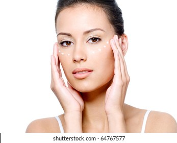 Close-up portrait of beautiful young woman's face with point of rejuvenating cream under the eyes - isolated