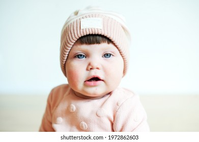 Closeup portrait of beauty baby girl with blue eyes in pastel color fashion pink and grey outfit indoor