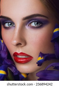 Close-up portrait of beauty young woman with purple eyeshadows and red lips with iris flowers