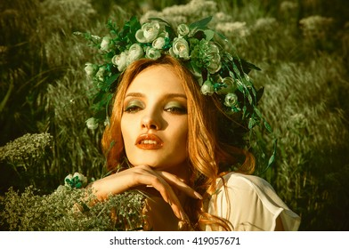 Closeup portrait of beauty young woman with nice makeup and wreath on head looking away in the grass