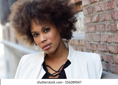 Close-up portrait of black woman with afro hairstyle standing in urban  background. Mixed d191dc850
