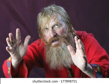 close-up portrait of the blessed with a long beard and a mustache and wet blond hair in a red shirt studio