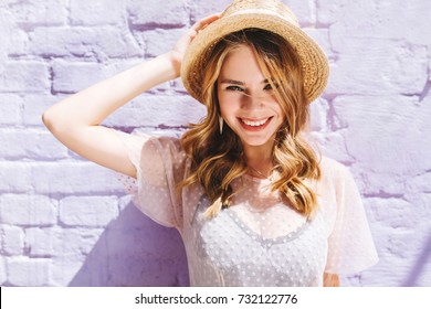 Close-up portrait of blissful blonde lady with broad smile posing in sunny day near old wall. Outdoor photo of laughing girl in white clothes and trendy straw hat enjoying good weather in weekend.