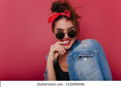 Close-up portrait of blissful lady in elegant sunglasses playfully posing on dark background. Studio photo of refined european girl with red ribbon having fun alone.