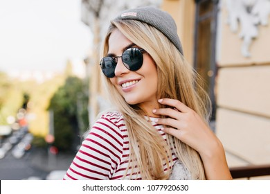 Close-up portrait of blissful pale girl having fun alone in weekend. Photo of charming blonde lady wearing trendy striped attire and enjoying good warm day.