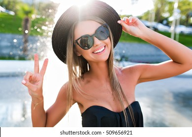 Close-up portrait of a blond girl with long hair posing in park on fountain background. She wears black sunglasses, hat, T-shirt. She is smiling and looking happy.