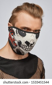 Close-up portrait of a blond man, posing on a grey background. He is wearing black mesh tank top. His face is hidden by  black mask with skull print. His the hair is combed back.