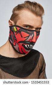 Close-up portrait of a blond man, posing on a grey background. He is wearing black mesh tank top. His face is hidden by black mask with monster print. His the hair is combed back.