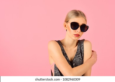 Closeup portrait of blond model with ponytail in melange gray sleeveless blouse wearing big black sunglasses isolated on pink background. Summer eyewear fashion.
