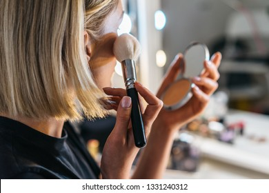 closeup portrait of blond woman who do make up with brush and powder in a room with professional lights. pretty middle age female make up one's face