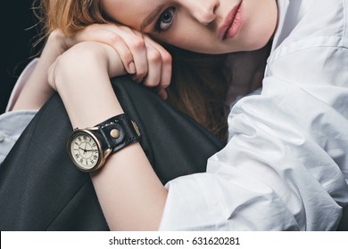 Close-up portrait of blonde fashion girl posing with vintage watch on hand, studio shot