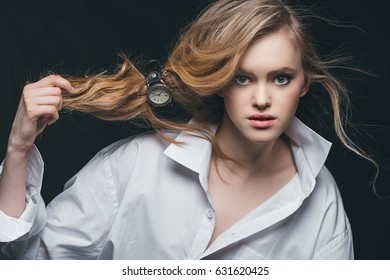 Close-up portrait of blonde fashion girl tying hair with vintage wrist watch, studio shot