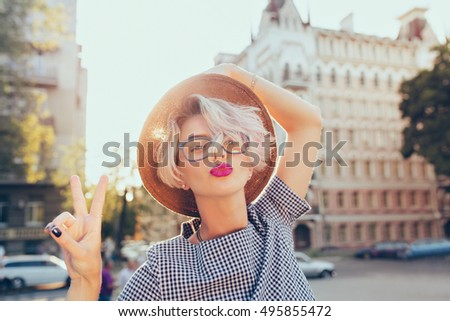 Closeup portrait of  blonde girl with short hair having fun  on the street on sunset background. She wears gray checkered  dress, glasses, hat . She makes a kiss to the camera.