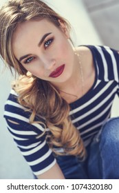 Close-up portrait of blonde woman, model of fashion, possing in urban background. Beautiful young girl wearing striped t-shirt and blue jeans in the street. Pretty russian female with pigtail.