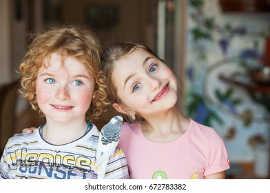 A close-up portrait of a boy and a girl in a house with a parrot on his shoulder, friendship, love, brother and sister with bird