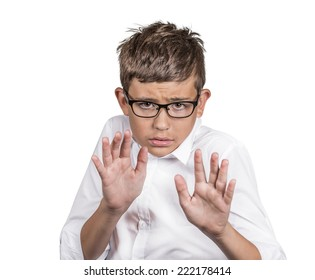 Closeup portrait boy with glasses looking shocked scared trying to protect himself from unpleasant situation isolated white background. Negative human emotion facial expression feeling body language