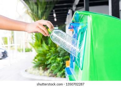 Closeup portrait a boy hand throwing empty plastic water bottle in recycling bin.