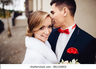 Close-up portrait of a bride and groom standing on the city street and lovely hugging