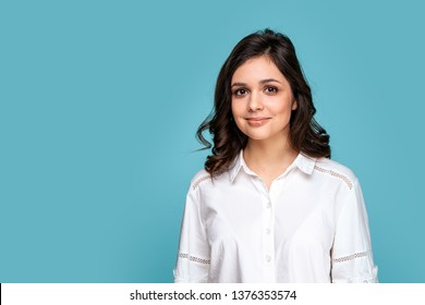 Closeup portrait of brunette beautiful girl in a white blouse isolated over the blue background.