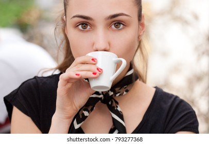 Closeup portrait of brunette beauty drinking espresso.