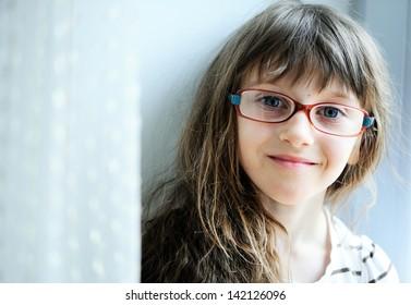Close-up portrait of brunette child girl in glasses