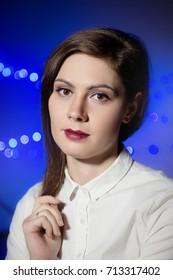 close-up portrait of brunette with clear skin and stylish make-up on the background with blue bokeh