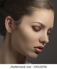 close-up portrait of brunette female with red glossy make-up turned of three quarters on gray background