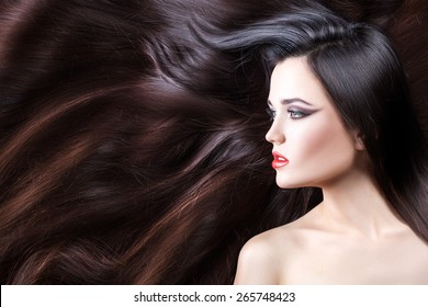 Close-up portrait of brunette girl in profile. She has long wavy hair.