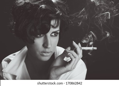 Close-up portrait of a brunette woman smoking a cigarette on black background
