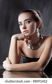 closeup portrait  of brunette woman wearing silver jewellry looking far wawy