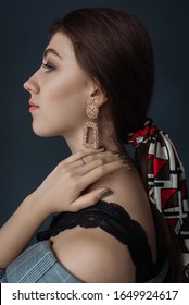Close-up portrait of a Brunettes with big earrings. Gold earrings close-up. Silk hair scarf. Tender handsome european girl with dark hair posing with naked shoulders, touching neck with hands.