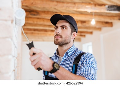 Close-up portrait of a builder worker decorator painting wall indoors