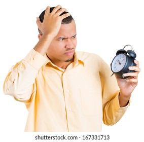 A closeup portrait of a business man, student, leader holding a clock very stressed, pressured by lack of time, running out of time, late for the meeting, isolated on a white background. Emotions