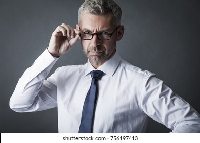 Closeup portrait of businessman looks through glasses at us on gray background