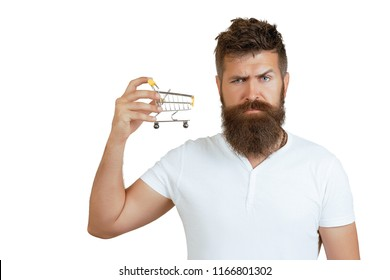 Closeup portrait of businessman showing mini shopping cart, online shop, ecommerce concept. e-commerce and shopping concept. Bearded man wearing white t-shirt holding mini shopping cart on right hand.