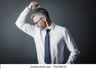 Closeup portrait of businessman, smelling, sniffing his armpit, something stinks, very bad, foul odor situation on a gray background