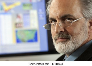 Close-up portrait of a businessman wearing eyeglasses and looking at the camera with a computer monitor in the background. Horizontal shot.