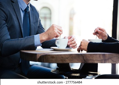 Closeup portrait of a businessman`s and businesswoman`s hands on the table with coffee