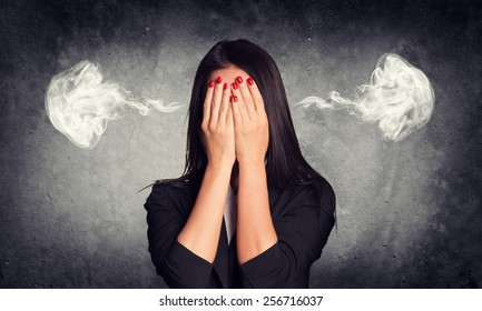 Close-up portrait of businesswoman hiding her face in her hands, with smoke from her ears. Raw concrete wall as backdrop