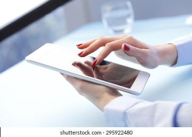 Close-up portrait of businesswoman holding hands digital tablet and touching the screen. Young professional working with tablet.