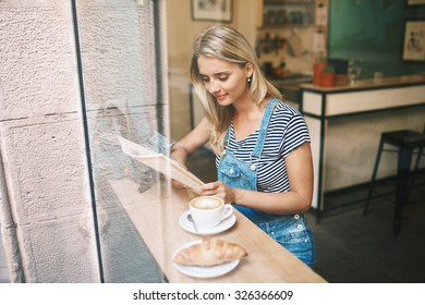 Closeup portrait of cafecity lifestyle woman sitting in trendy urban cafe reading magazine and drinking coffee with a croissant during your vacation