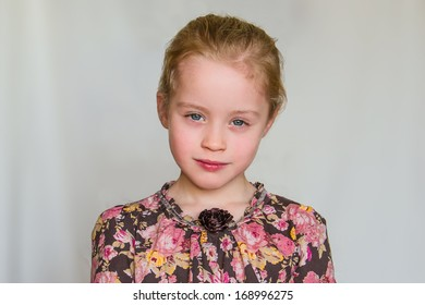 Closeup portrait of calm preschool girl with strawberry blonde hairs and flowered dress who looks into the lens against the light grey background