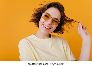 Close-up portrait of carefree white girl plays with short wavy hair. Photo of elegant european woman with black tattoo isolated on yellow background.