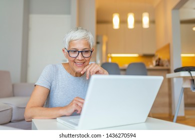 Close-up portrait of casual woman using her laptop while sitting on couch and working. An attractive middle aged businesswoman sitting in front of laptop and managing her small business from home.