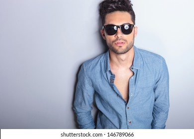 closeup portrait of a casual young man with sunglasses looking at the camera. on gray background