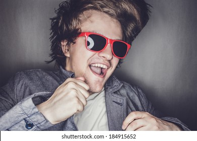 closeup portrait of a casual young man with sunglasses jumping